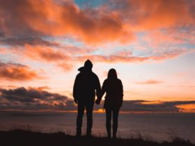 Silhouette photo of man and woman on cliff while sunset