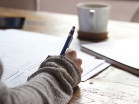 Person writing on brown wooden table near white ceramic mug and notepad