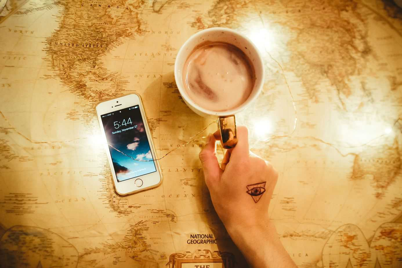 Person's hand holding a mug with coffee next to an iphone and on top of a world map