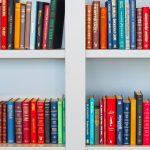 Lots of books placed on white wooden shelf