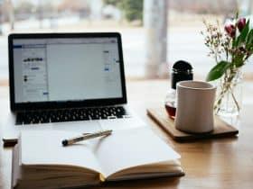 Laptop MacBook near coffee, a pen and an open book