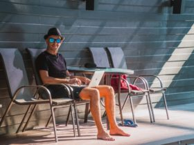 Man outdoors using laptop in the pool area