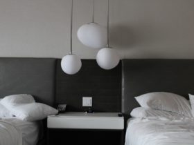 Two hotel beds with lights in between