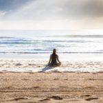 Woman sitting on seashore in Manly Beach, Australia