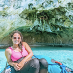 Michelle smiling at the camera while wearing sunglasses and entering a cave in a small boat