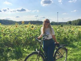 Rubby smiling while riding her bike near a field of sunflowers