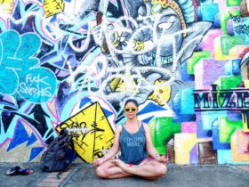 Jade doing yoga in front of a wall with graffiti