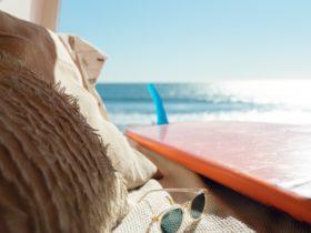 Silver framed sunglasses next to surfboard near ocean