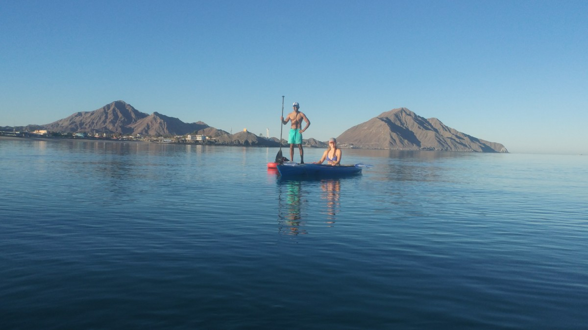 Julie sits in a blue kayak on a lake while Reet stands on a red stand-up paddboard