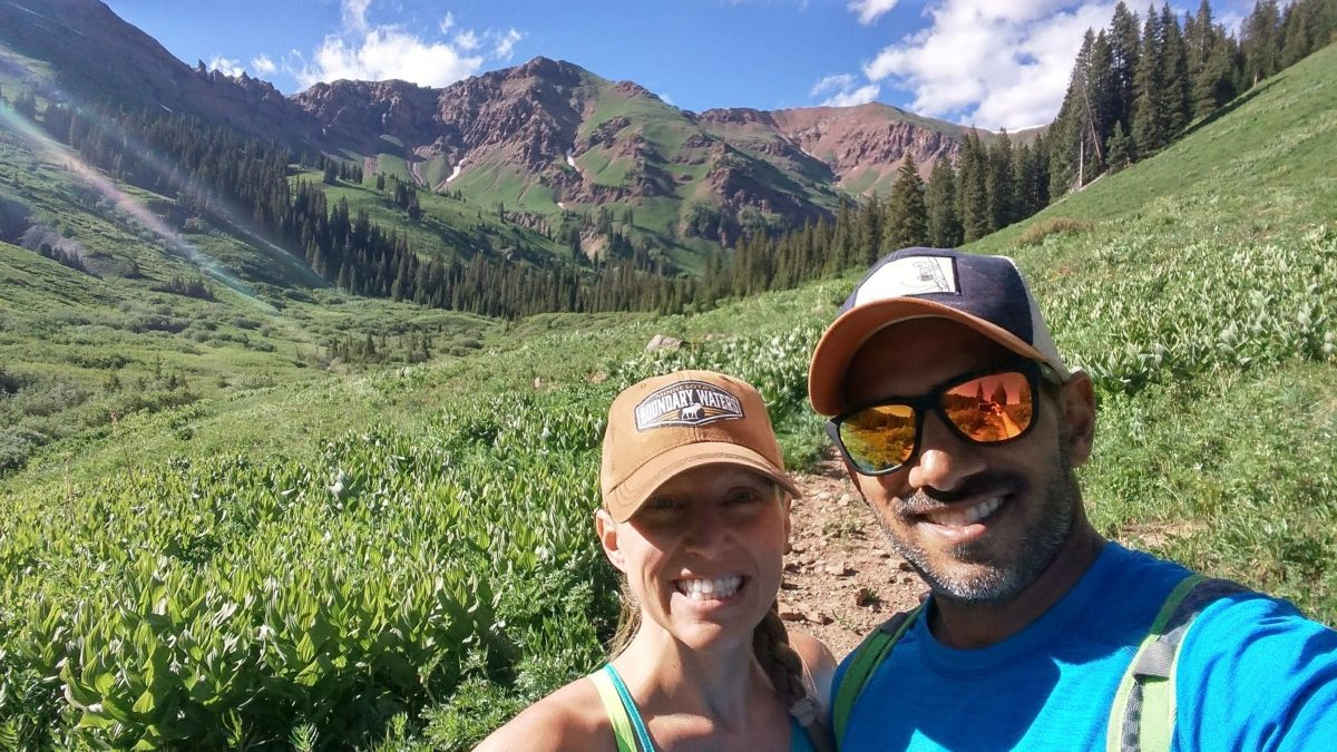 Julie and Reet from TripOutside smile while hiking with a lush field and mountain behind them