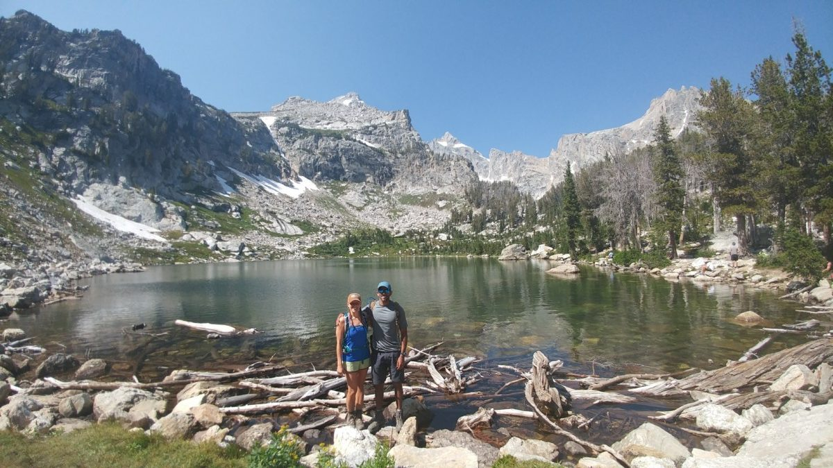 Julie and Reet Singh stand in front on an alpine lake on a sunny day with sparse trees and some higher mountain peaks behind them