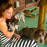 Jane Thomas sits on a front porch with one dog cuddling her and another dog sitting at her lap
