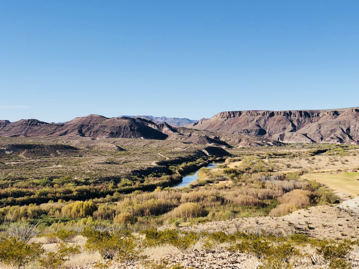 a large field in Big bend national park with a river running though the image and a long, flat mountain range spanning the length