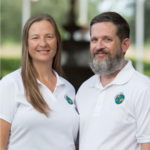 Sean and Julie chickery wear matching white polo shirts, slightly facing once another and smiling with a blurry background behind them