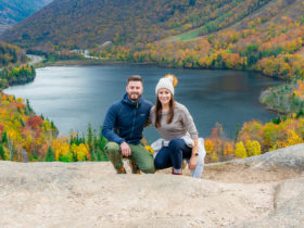 Mark and Kristen Morgan squat on a rock with a large lake behind them surrounded by trees with vibrant fall colors