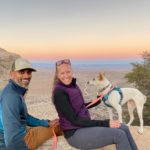 Julie and Reet Singh sit atop a rock with their small dog smiling at the camera with a multicolored sunset in the background