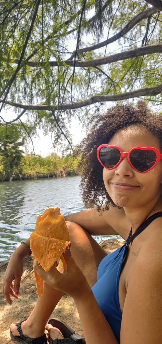 Felly day sits by a lake with a peeled mango in her hand while wearing red, heart-shaped sunglasses