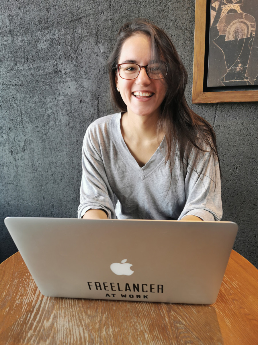 Deya sits at a table with her laptop open in front of her smiling and wearing glasses