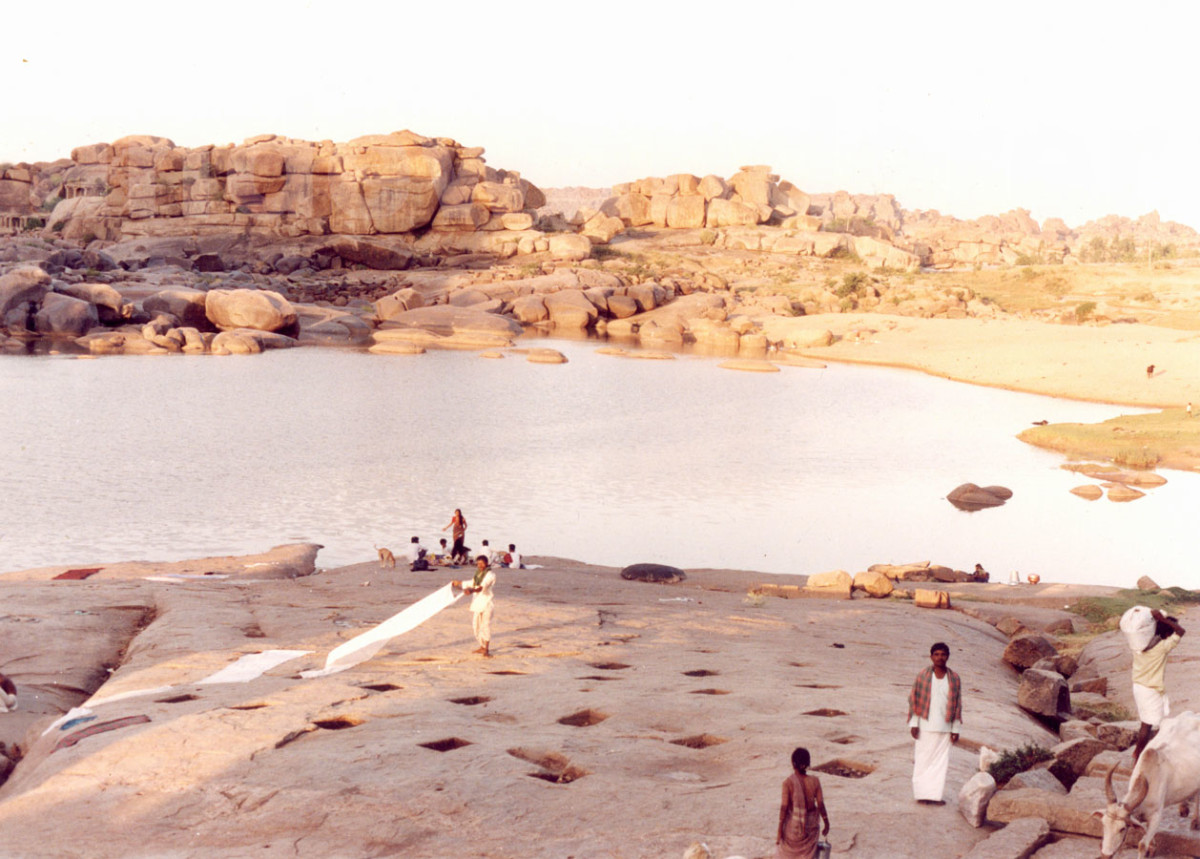 large boulder formations in hampi, india while people stand on the rocks that slop down to a lake