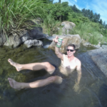 Cam Woodsum smiling and enjoying a beer in a sunny day in the lake