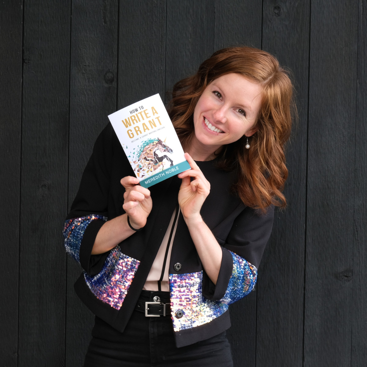 Meredith Noble stands holding a book she wrote in her hands near her face while smiling
