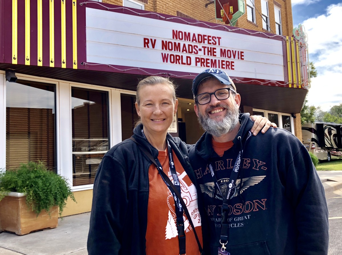 """Sean and Julie chickery stand in front of a movie theatre sign that says """"nomadfest rv nomads the movie world premiere"""""""