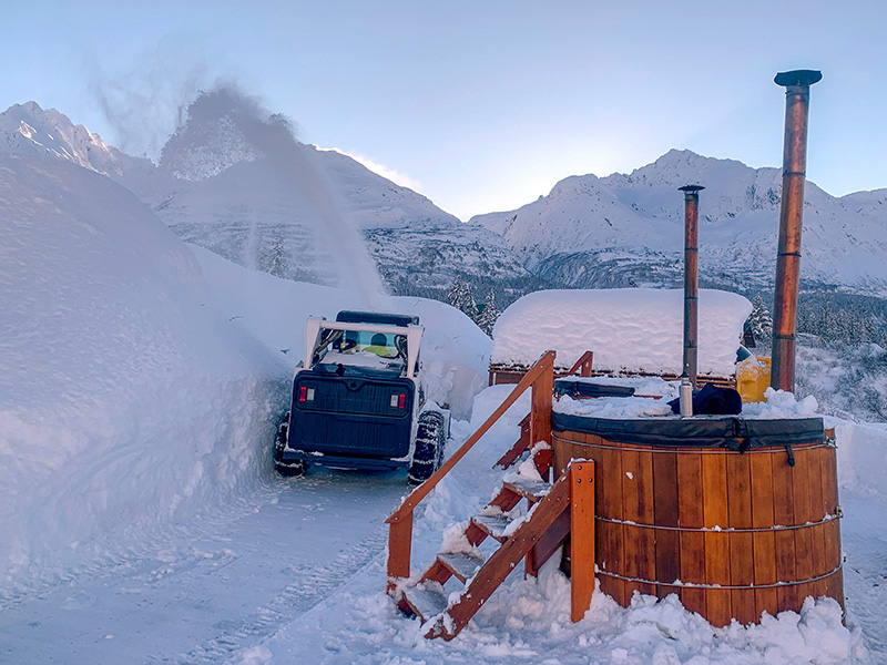 wooden hot tubs sit in deep snow with staircases leading up to them in valdez, alaska