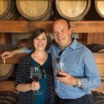 Greg and Betsy enjoying a glass of wine in front of some wine barrels in a winery in Palermo, Italy