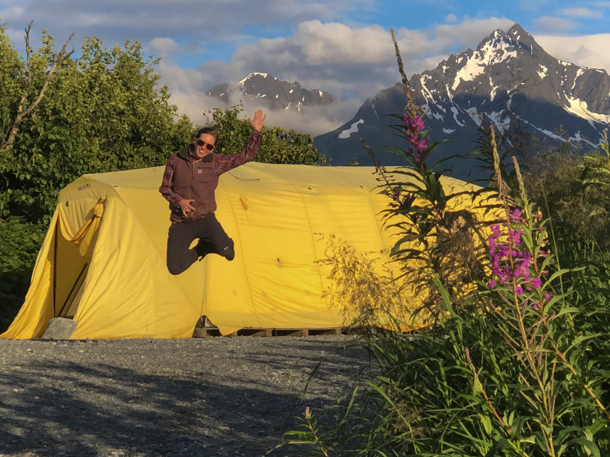 Meredith Noble jumps in the air in front of a huge yellow tent in Alaska with fireweek in the foreground and a snow-capped mountain behind the yellow tent