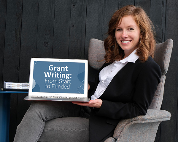 """Meredith noble sits facing to the right in a large chair with her legs crosses holding a laptop with a screen saying """"grant writing: from start to funded."""""""