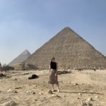 Sarah Archer stands in front of a pyramid in Egypt in the sun