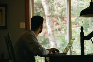 Man in gray hoodie using laptop while looking to the outside