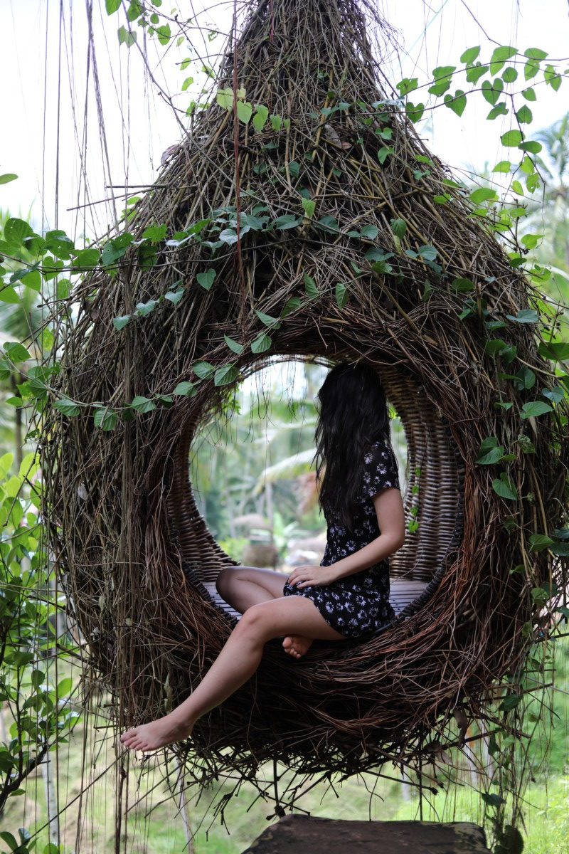 Deya sits in a swinging chair meant to mimic a bird's nest in Bali