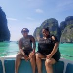 Corritta Lewis sits on the side of a boat with emerald green ocean and tall cliffs behind in Thailand