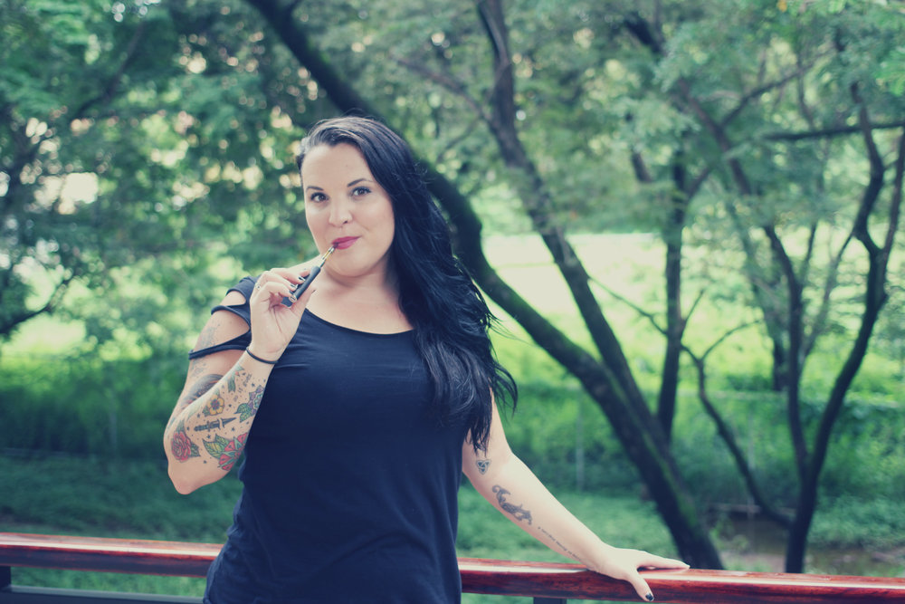 A women stands with one arm on a railing and another holding a vape pen in front of a green landscape with trees
