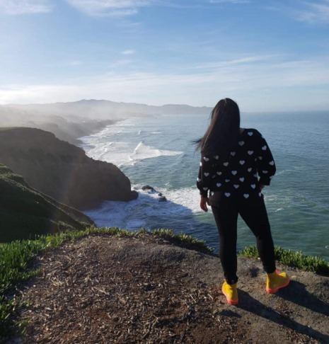 A women stands at the edge of a cliff overlooking the ocean below in San Francisco, California
