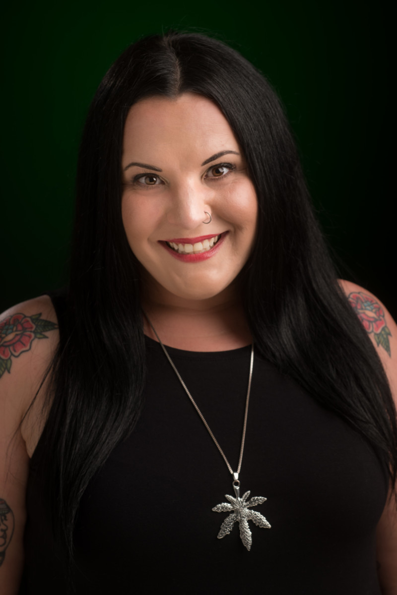 A professional photo of a woman wearing a black tank top with a long necklace and tattoos on her arms