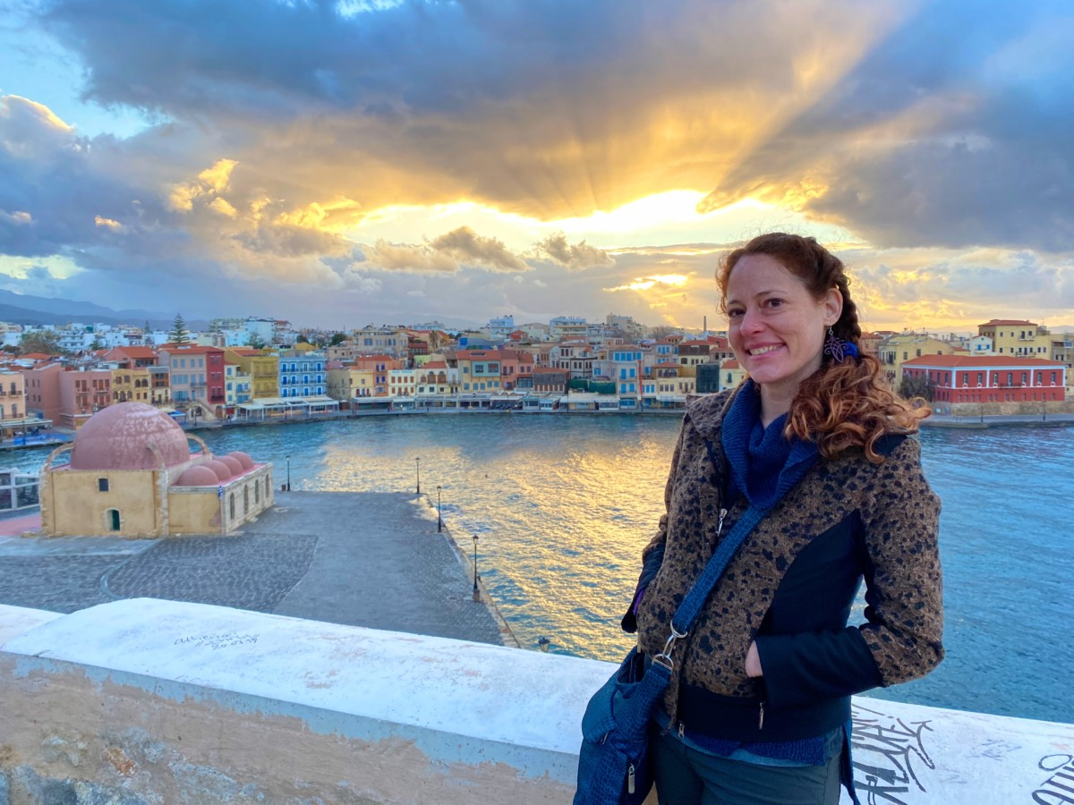 Nora Dunn stands in front of the setting sun in Crete with many buildings and the ocean behind her