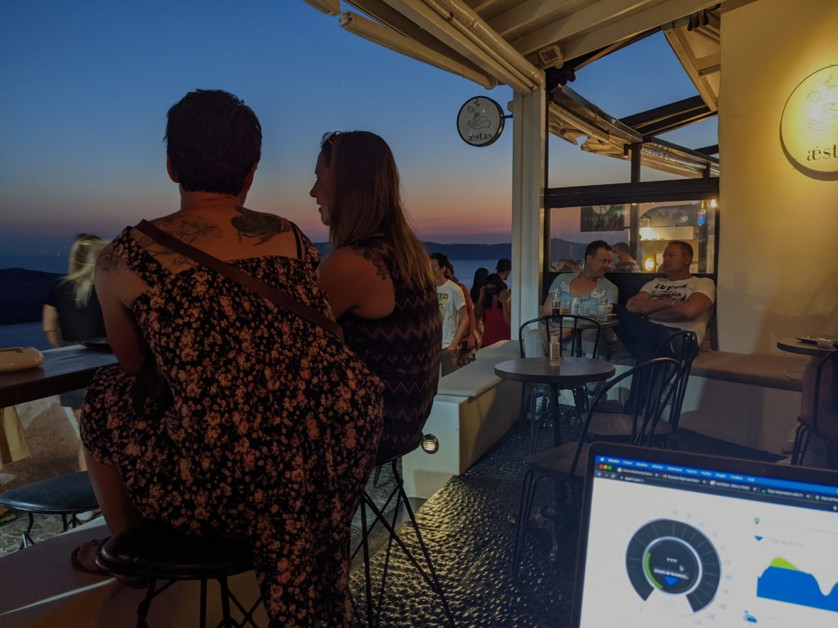A man and a woman sit at a bar facing the sunset in Santorini, Greece