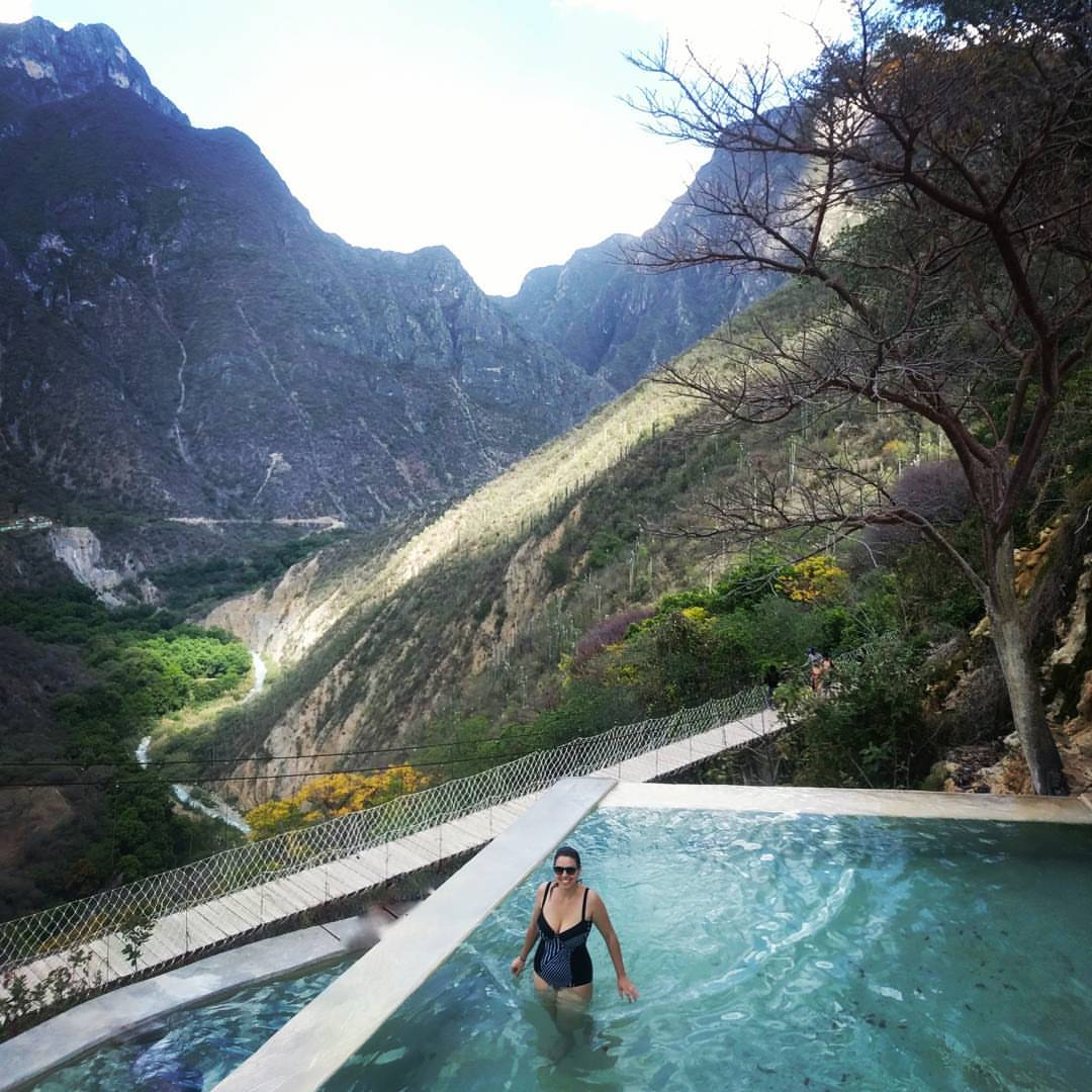 Lolly stands in a swimming pool that is next to a large and long suspension bridge with tall mountains surrounding the area