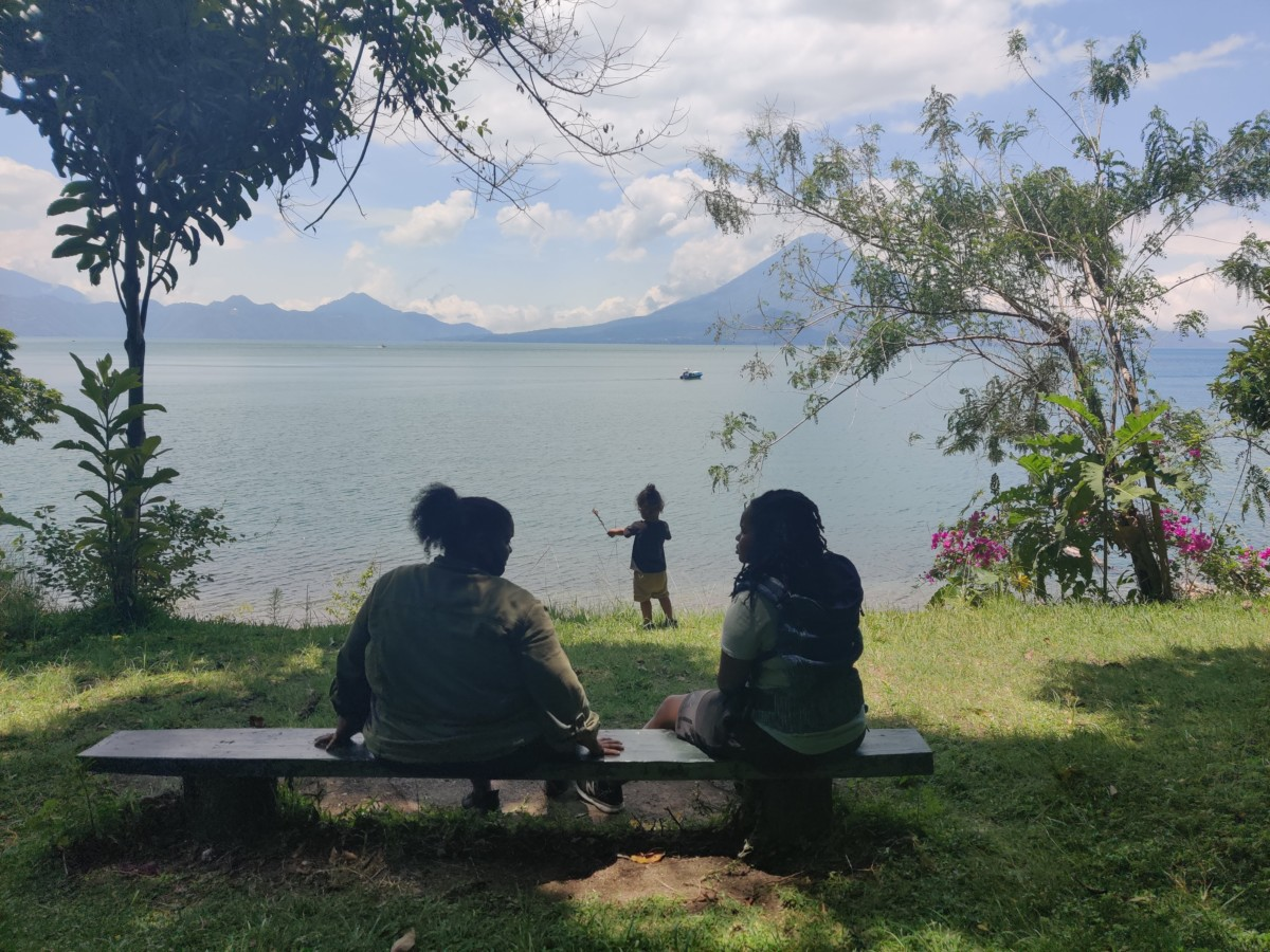 two women sit on a bench facing a lake while their small son plays near the lake's shore