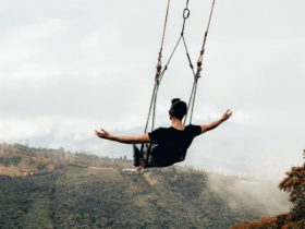 Blake Miner on a large swing with his arms out at his sides as he swings over a large valley