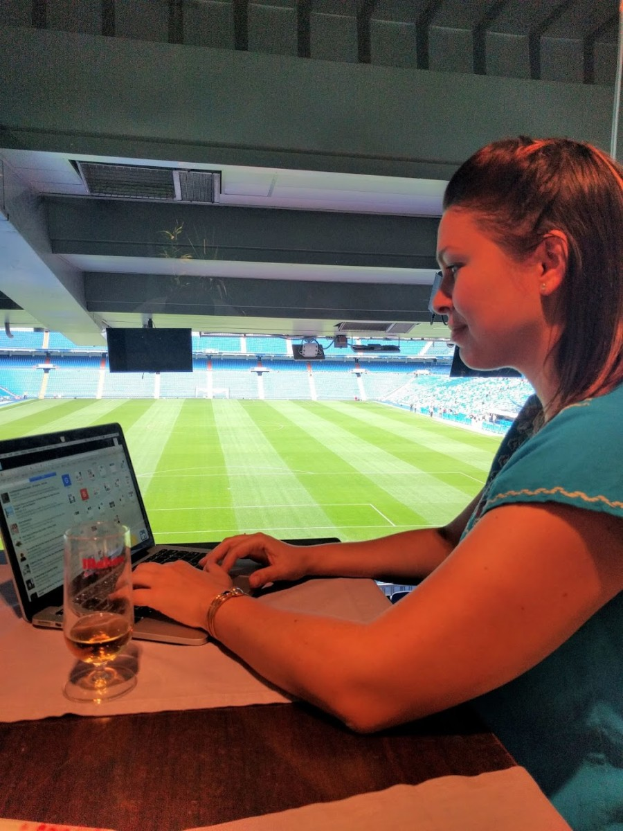 Lolly sits at a desk working on her computer at the Santiago Bernabeu in Madrid while a grass sports field is off to her right
