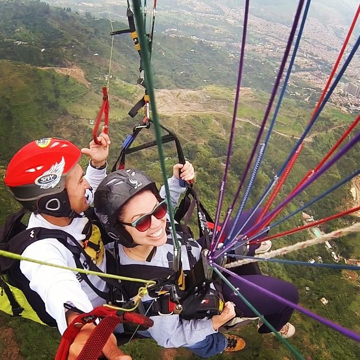 A photo from above shows lolly sitting below a parachute as she flies through the sky in Medellin