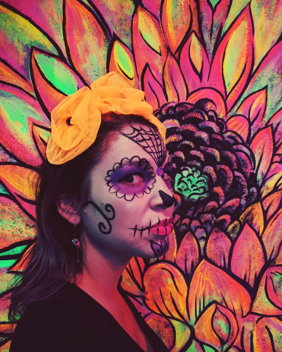 Lolly stands with her face painted in white and black and stands in front of a colorful painting of a flower