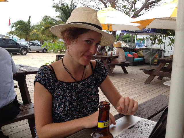 Nora Dunn sits at a table working on her laptop in the Caribbean