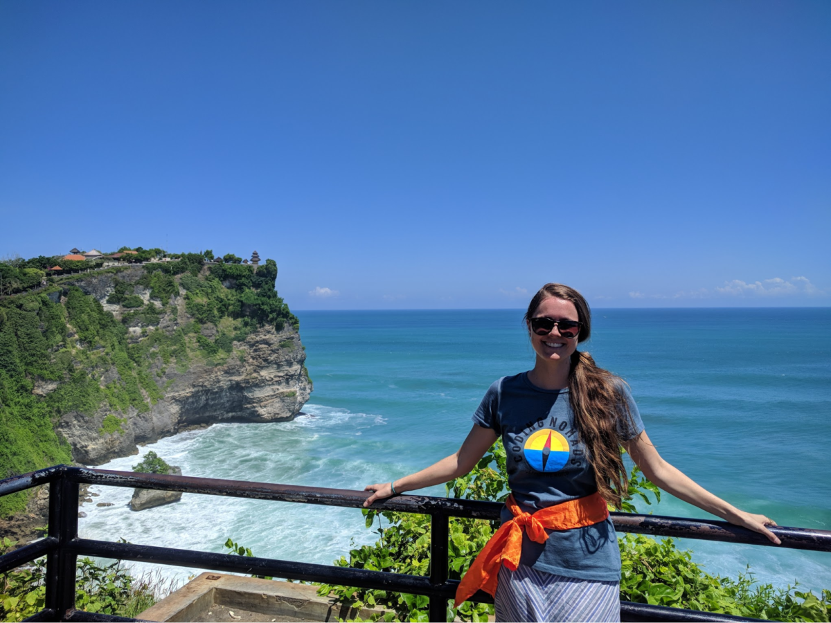 a woman stands with both arms and hands on a wooden railing on a cliff that overlooks the ocean