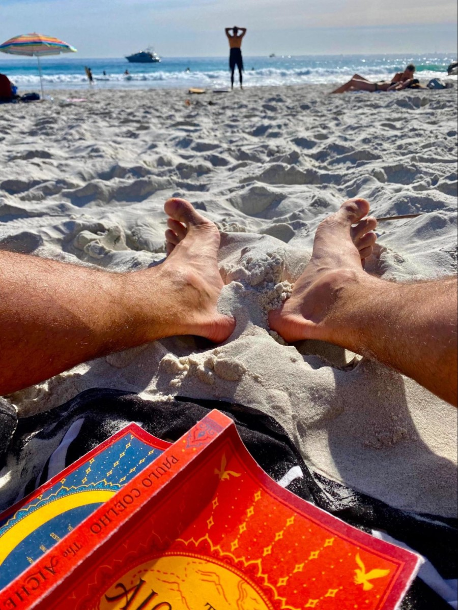 the book the alchemist sits open and face down on a towel on a sandy beach between a person's legs with the ocean nearby