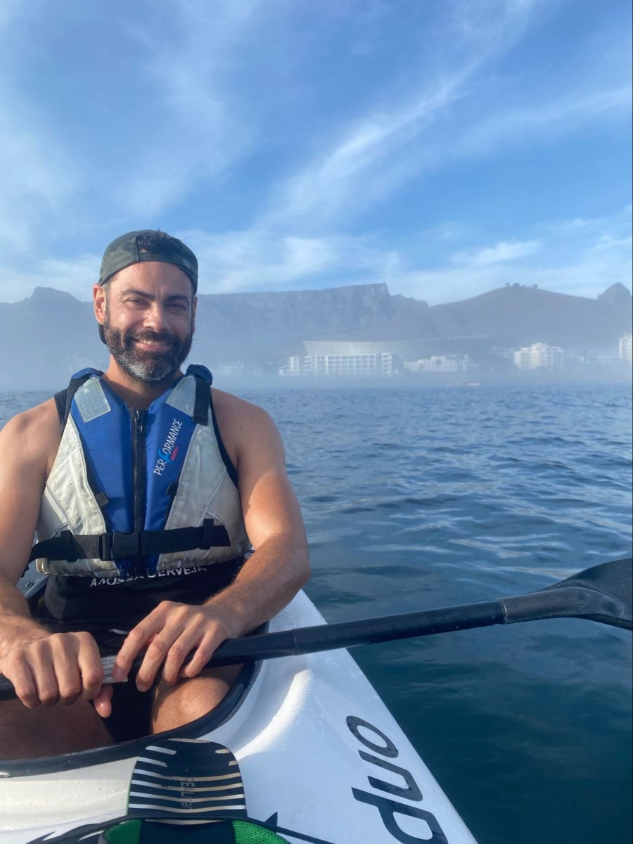 DIrk Bruwer sits in a white kayak on the ocean with the paddle sitting across the boat as he wears a life vest with cliffs in the background and some clouds in the blue sky