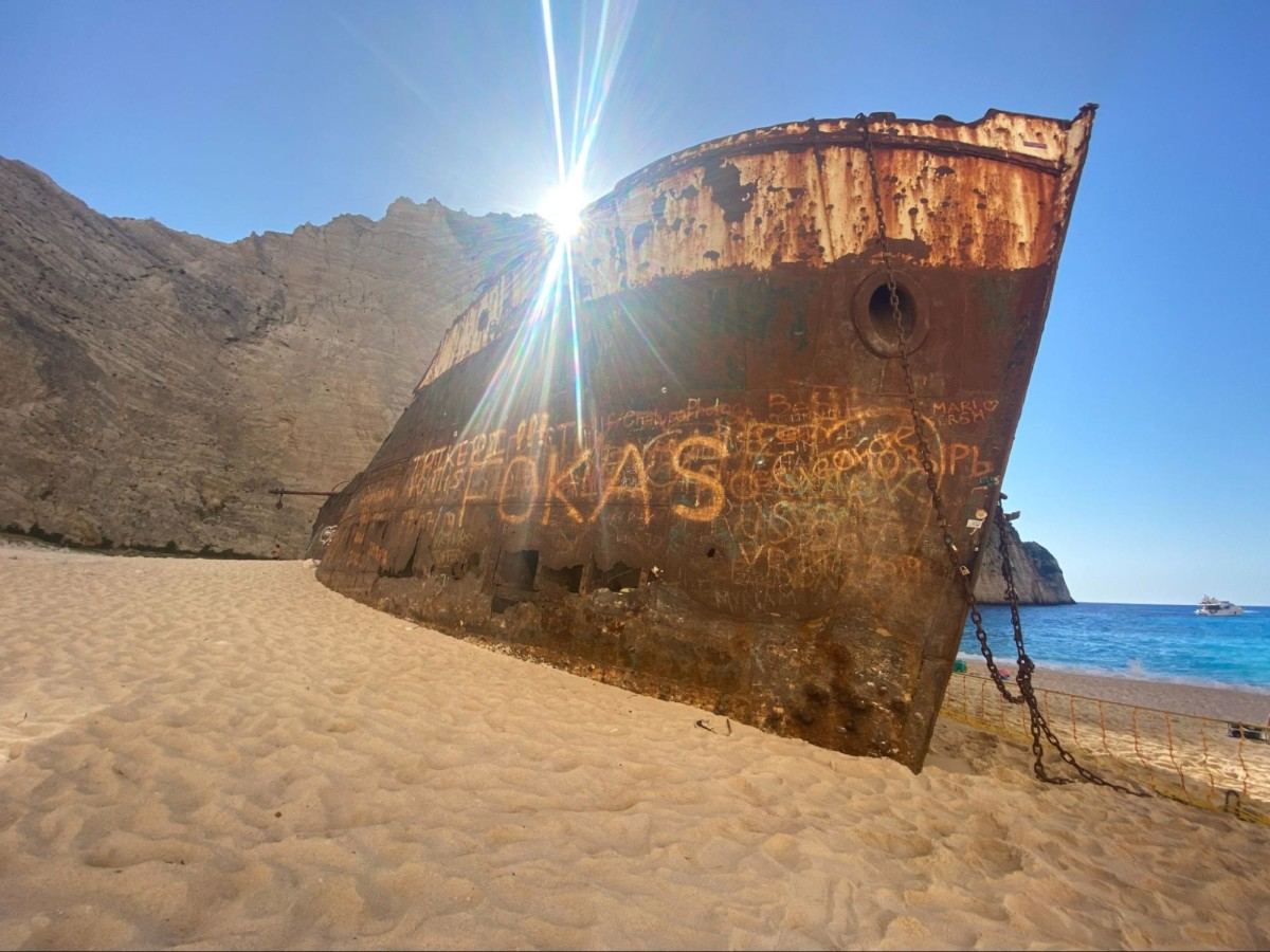 An old rusted boats sits on a sandy shore in Namibia with the sun shining over it and the ocean off the the right